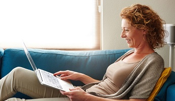 woman lay back on the sofa with a macbook on her lap