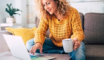 woman in a mustard knitted jumper looking at life insurance quotes