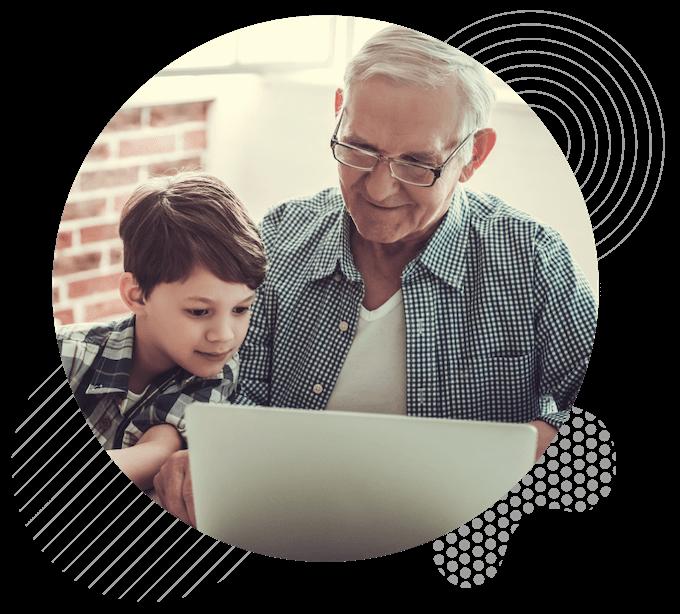Grandad showing grandson a computer
