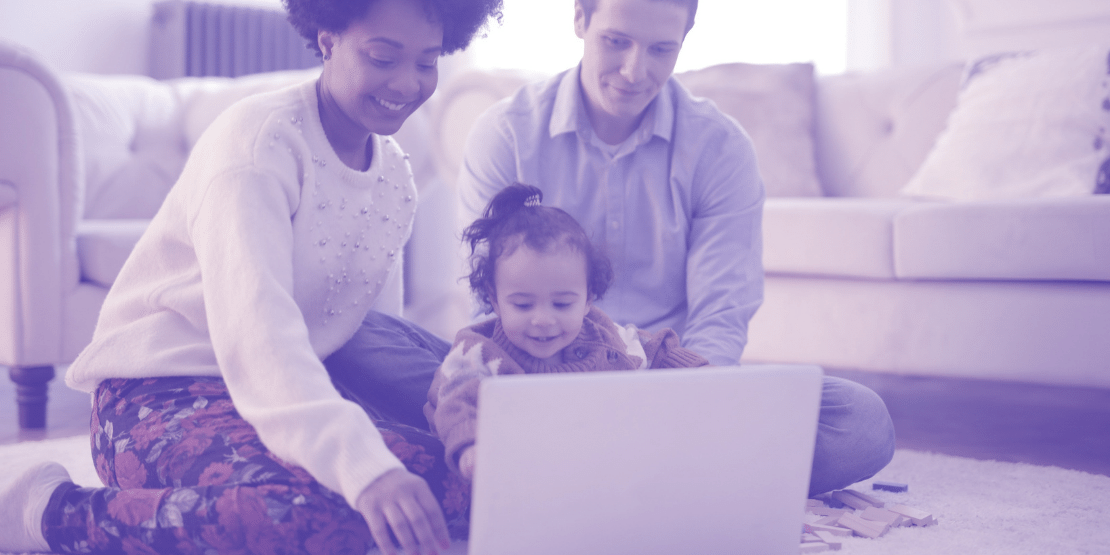Mum, Dad and Baby all sat round a laptop smiling in a family home.
