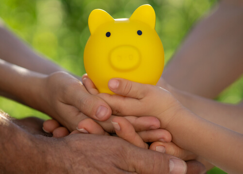 Family holding piggy bank in hands against green spring background.